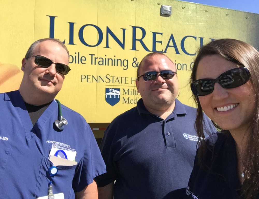 "Three people "" two men and one woman "" pose for a photo in front of a large trailer that has the word LionReach on it as well as the Penn State Health Milton S. Hershey Medical Center logo."