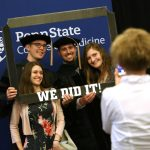 """Four people – two men and two women – pose for a photo inside of a hand-held frame with the words """"We did it!"""" across the bottom. The backdrop has a Penn State College of Medicine logo."""