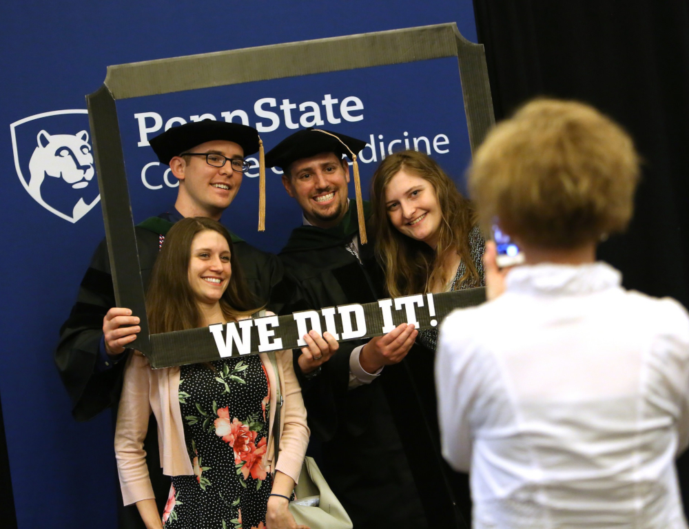 "Four people – two men and two women – pose for a photo inside of a hand-held frame with the words ""We did it!"" across the bottom. The backdrop has a Penn State College of Medicine logo."