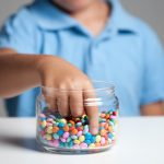 A jar of small, multicolored candies is in the foreground. A young boy stands behind the jar with his hand extending into it.