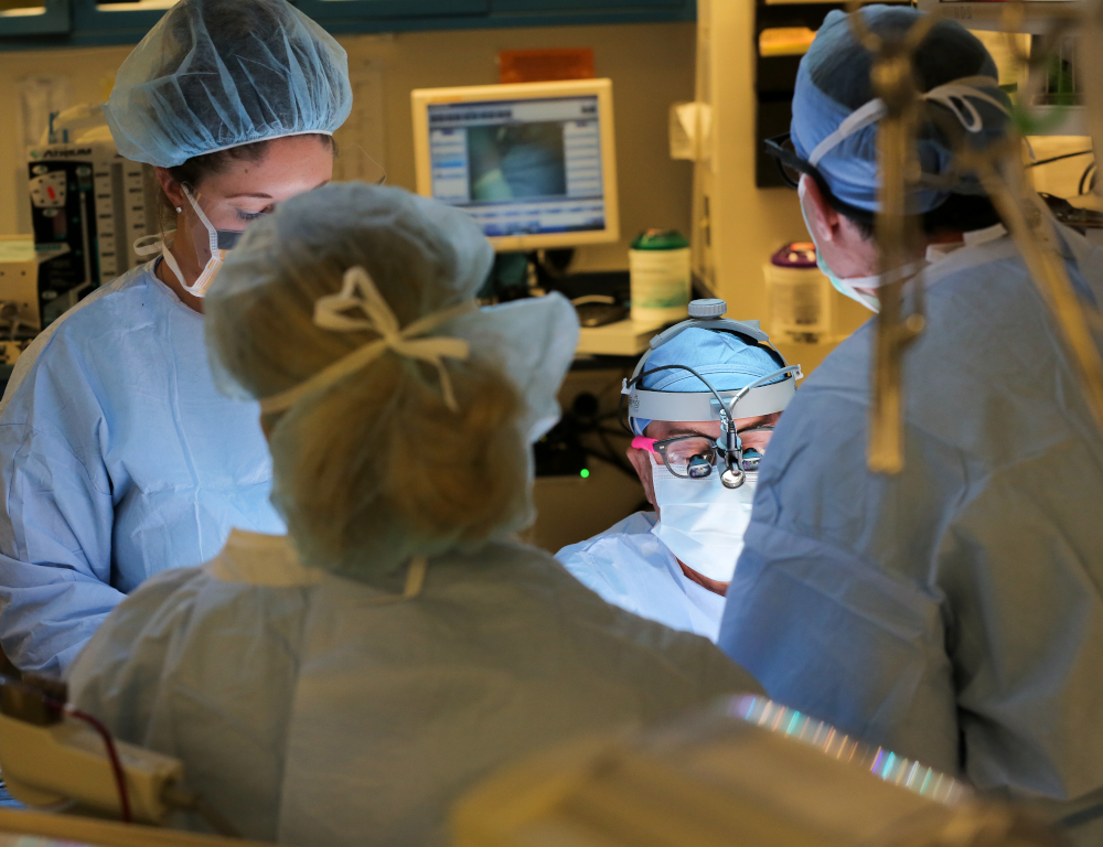 Four people in surgical scrubs and gowns are gathered around a patient in the operating room. A computer monitor and some equipment are visible in the background.