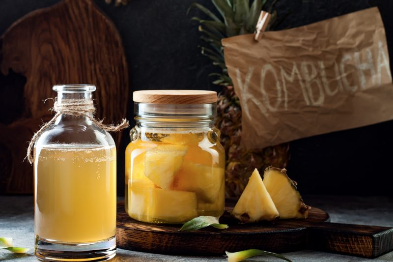 "In the foreground are two glass jars with yellow liquid, one containing pieces of pineapple. In the background is a pineapple and a sign reading ""KOMBUCHA."""