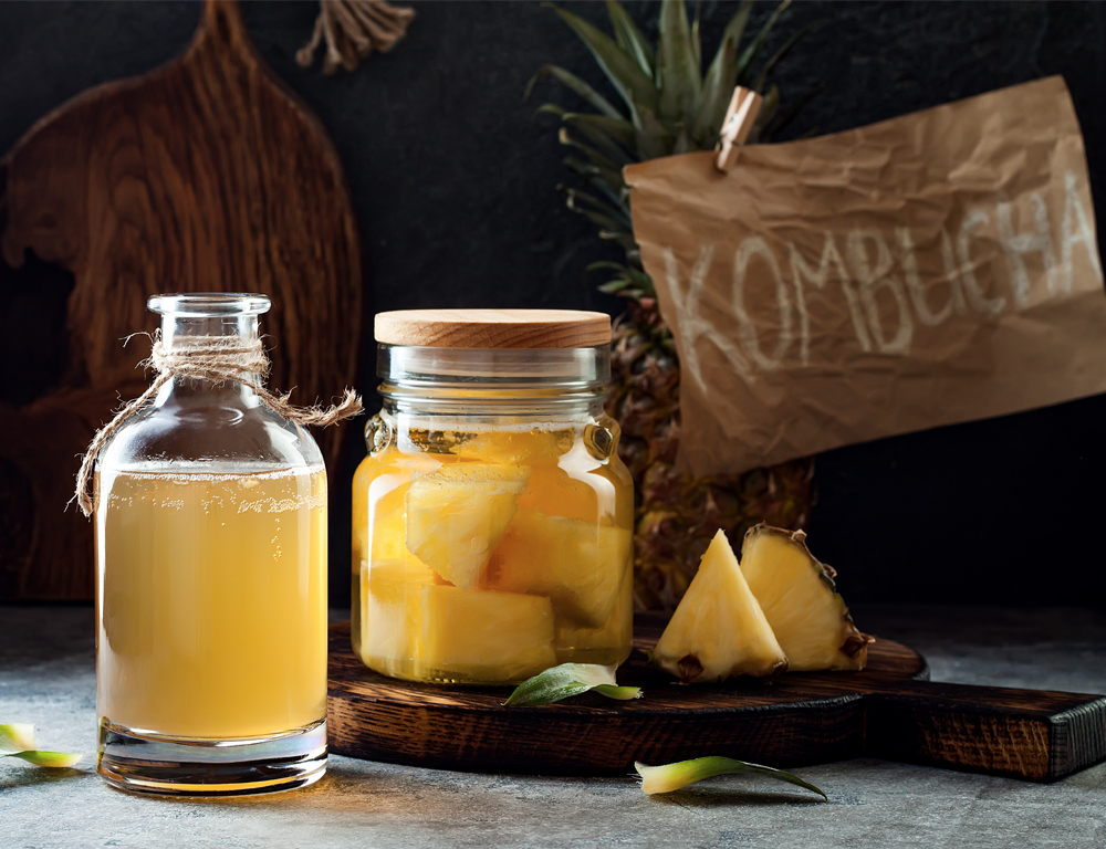 """In the foreground are two glass jars with yellow liquid, one containing pieces of pineapple. In the background is a pineapple and a sign reading """"KOMBUCHA."""""""