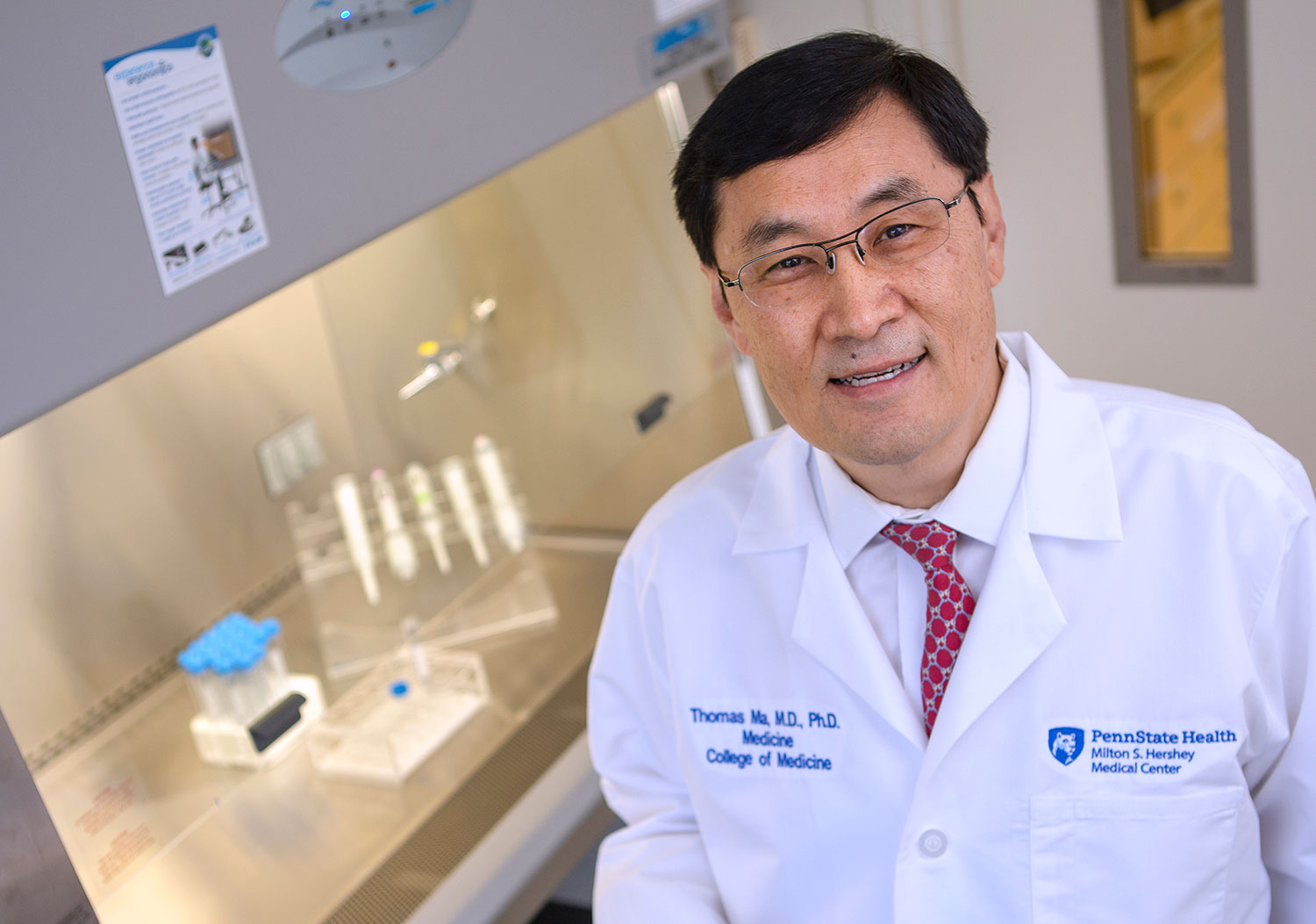 Dr. Thomas Ma aims to improve faculty work satisfaction and build a stronger research program at Penn State College of Medicine. Ma is pictured standing in a laboratory, wearing a medical coat, with lab equipment visible in the background.