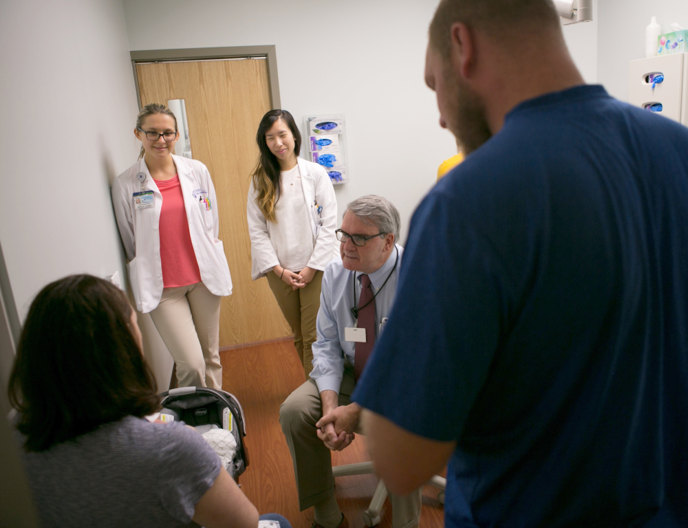 In a clinic room, a man in a tie speaks with a woman who's holding an infant and facing away from the camera. Three other people are in the room, standing and looking on.