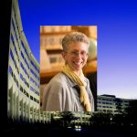 A woman with short hair and classes smiles for a photo in front of a bookshelf. The photo is superimposed over a photo of Penn State College of Medicine.