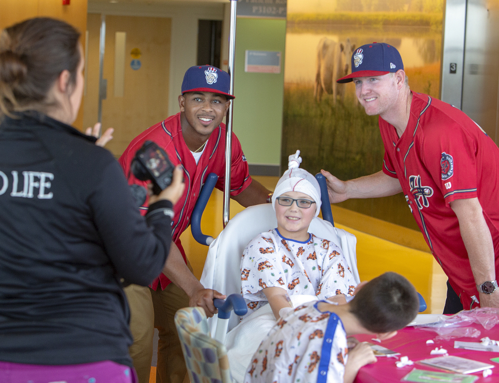 Two Harrisburg Senators baseball players stand on either side of a child in a mobile hospital bed while a woman standing to the side takes their picture.