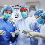 Three medical professionals dressed in operating room scrubs, caps and face masks stand in an operating room.