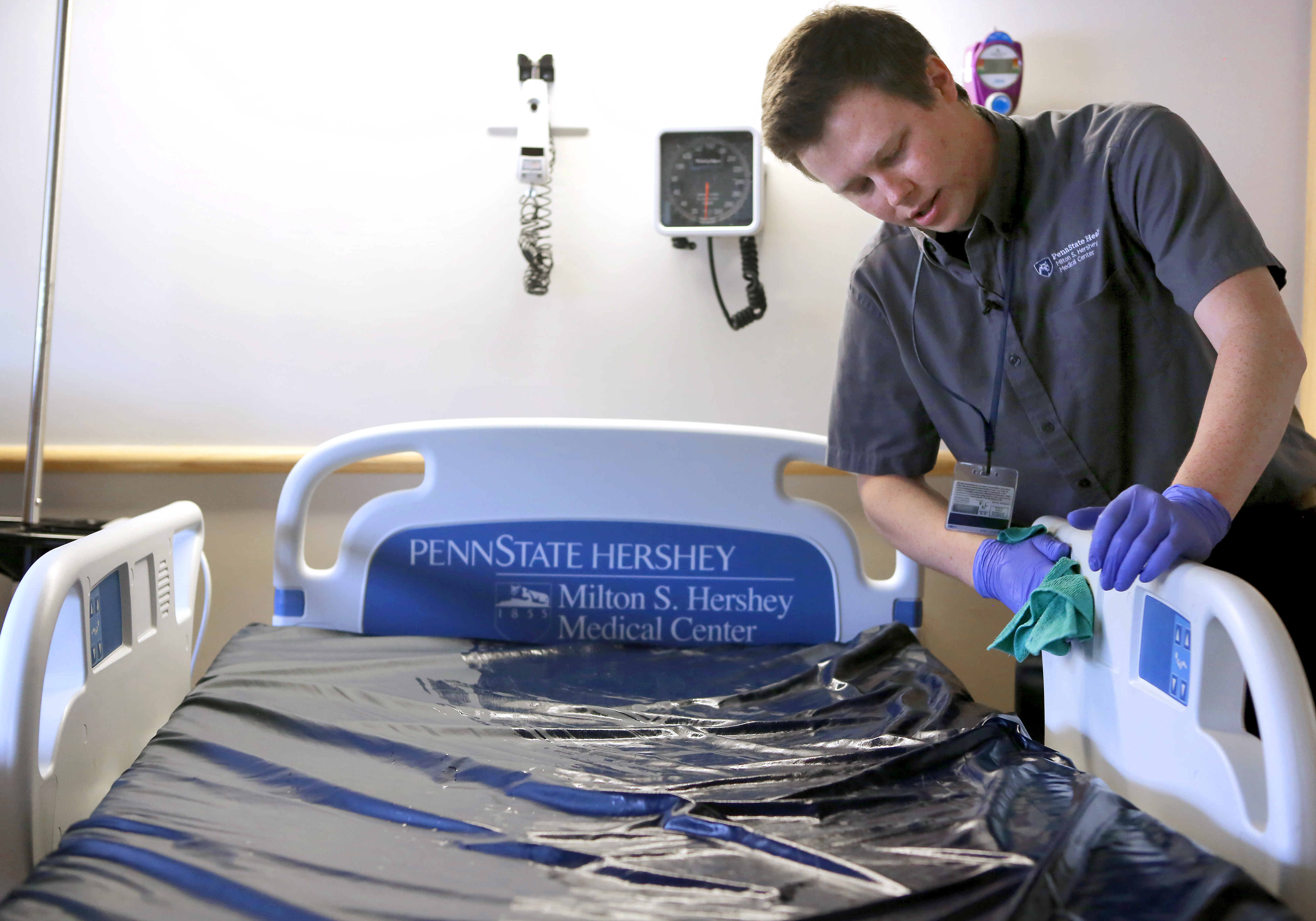 A young man wearing a button-down shirt with a Hershey Medical Center logo leans over a patient bed and wipes the side rail with a cloth. He is wearing purple gloves. The bed has a Hershey Medical Center logo on the headboard.