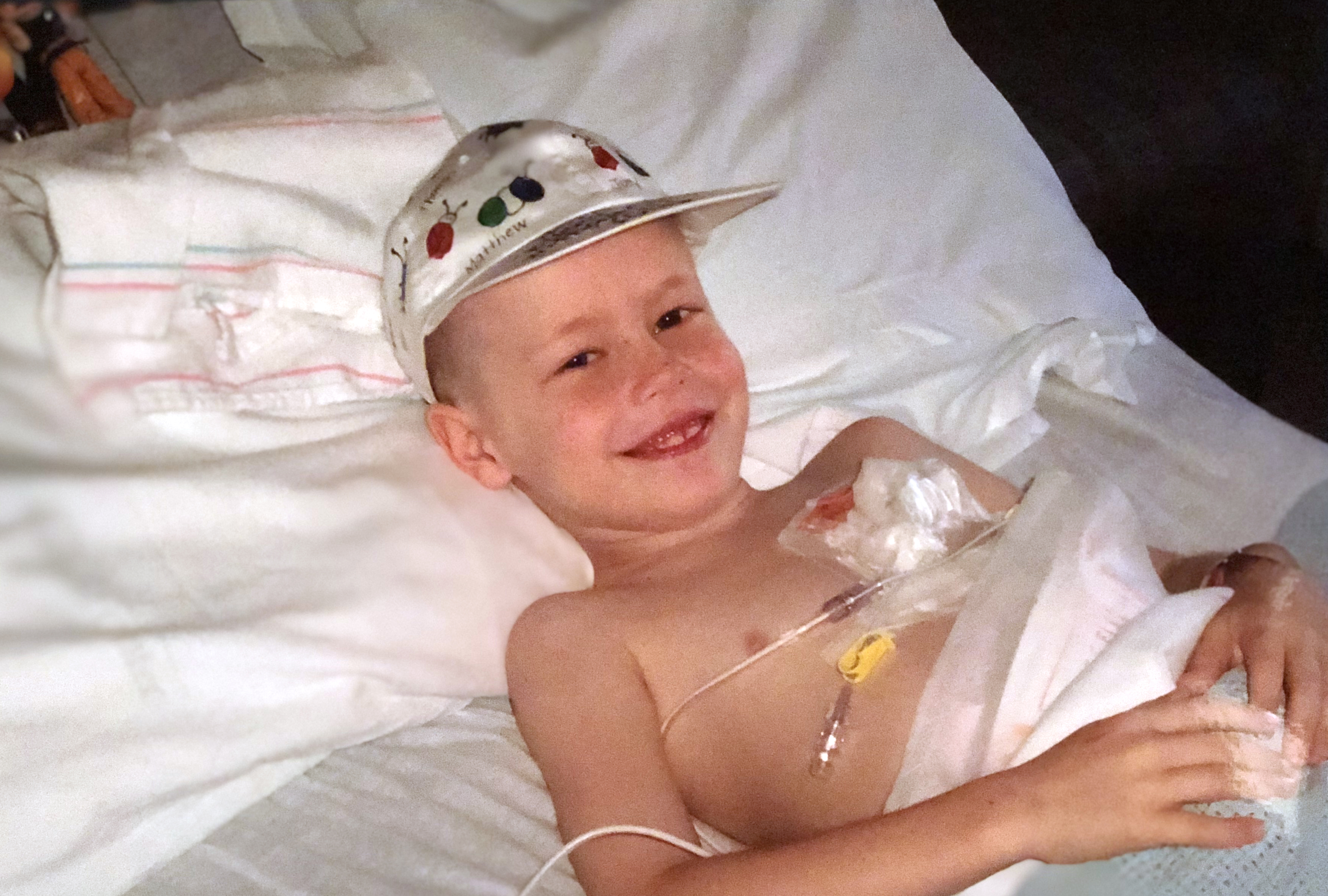 Cole Horne at age six smiles as he lies in a bed at Penn State Children's Hospital bed. He is wearing a silk baseball cap and has a port taped to his chest.