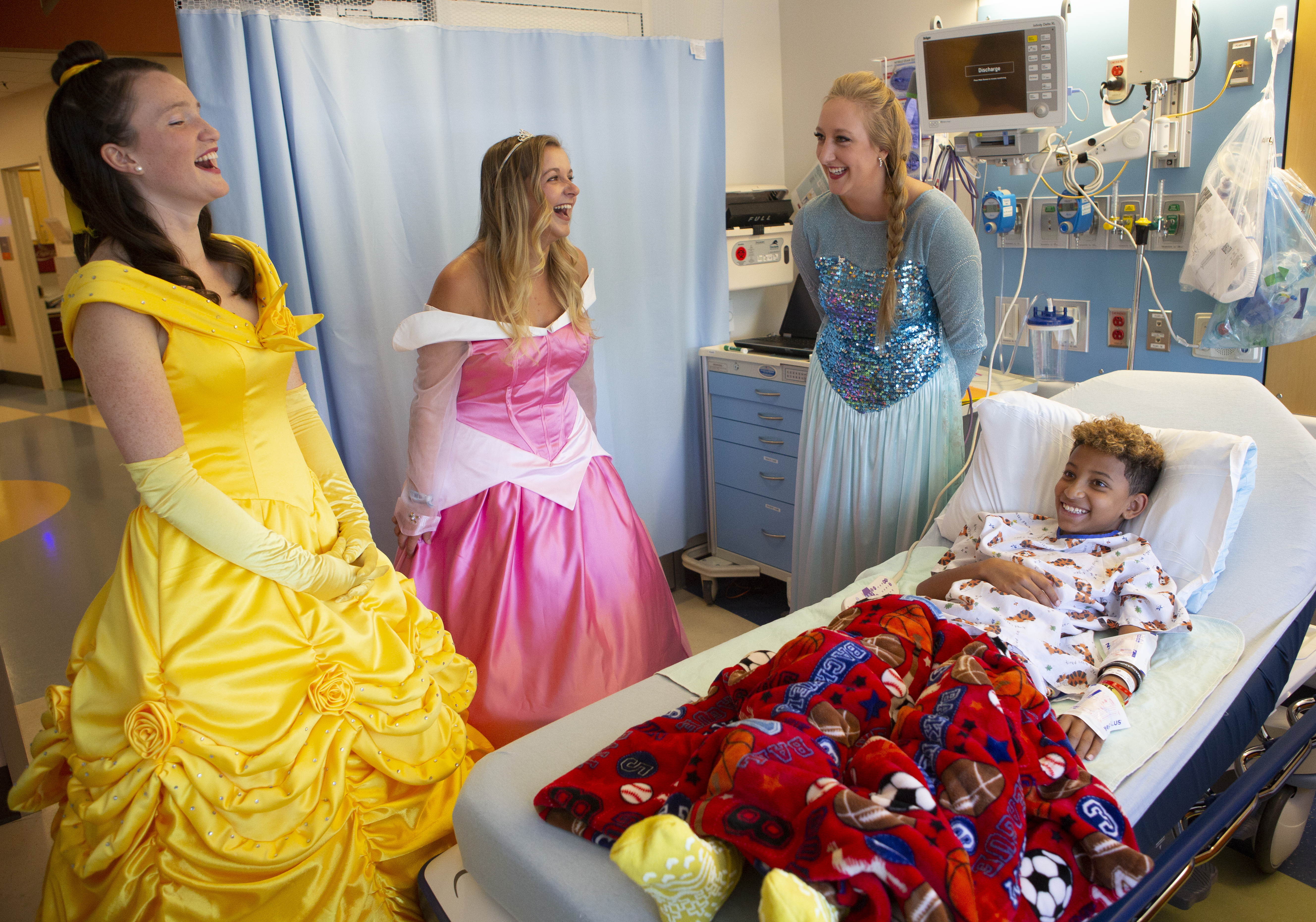 Three women dressed in princess costumes visit an 11-year-old boy at Penn State Children's Hospital. All four are laughing. The boy is lying in a hospital bed covered with a sports blanket.Three women dressed in princess costumes visit an 11-year-old boy at Penn State Children's Hospital. All four are laughing. The boy is lying in a hospital bed covered with a sports blanket.