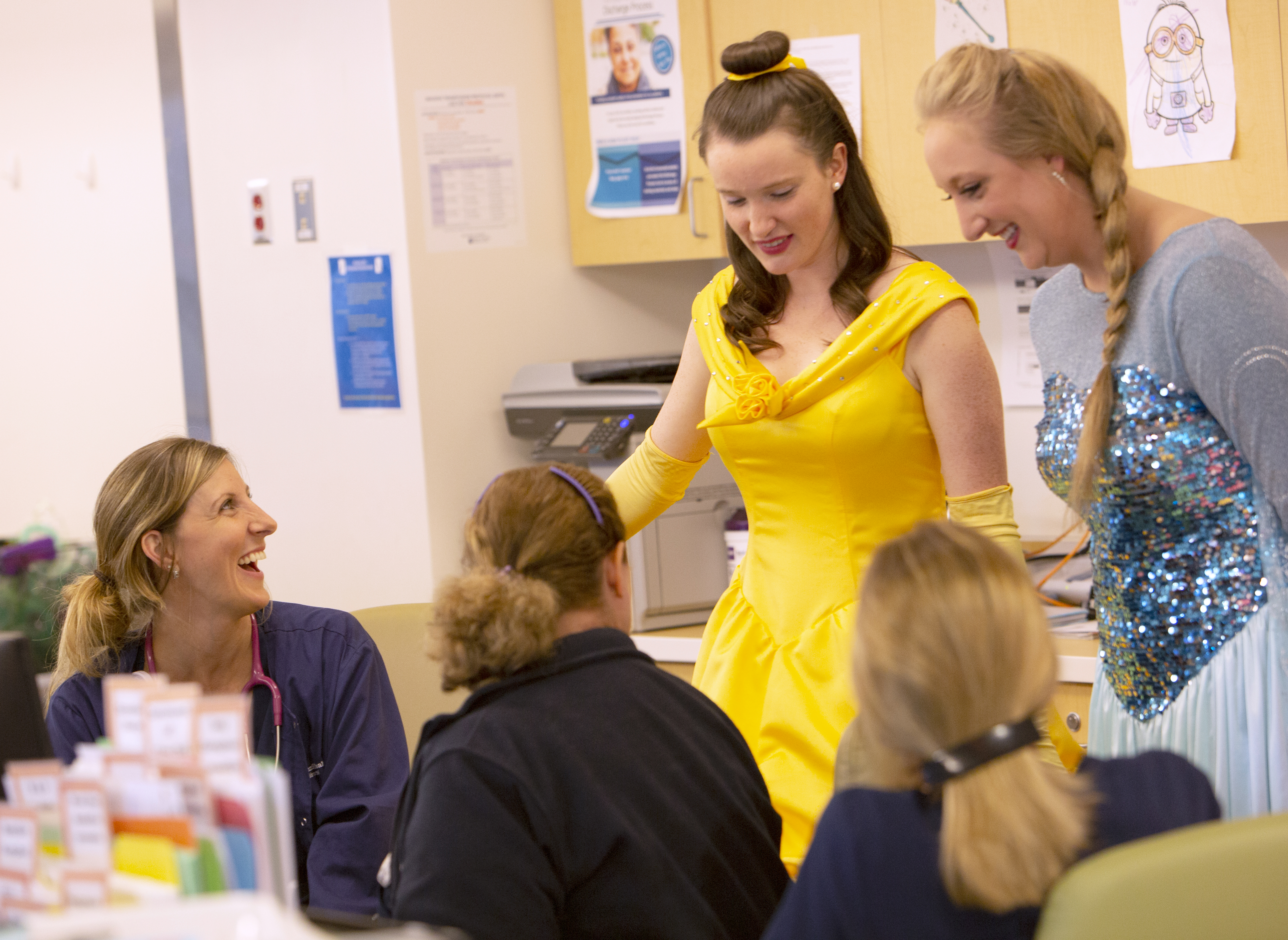 Two women dressed as princesses stand and talk to three nurses at Penn State Children's Hospital. The nurses are sitting in a nurse's station room. The woman on the far-left is smiling. The other two nurses are seen from behind. A copy machine is visible behind one of the princesses.