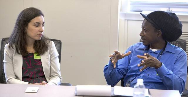 Julie Lentes, public health sciences instructor at Penn State College of Medicine, looks over at Lyndon Waterman, a student with University of West Indies-Cave Hill, Barbados, who is wearing a dark, floppy hat with a visor. The pair are seated at a conference table during a meeting between Global Health Exchange students and leaders of the Pennsylvania Department of Health.