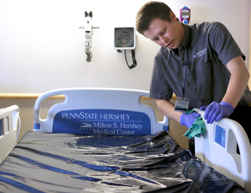 A man stands to the side of an empty hospital bed, using a cloth to scrub the side rail.