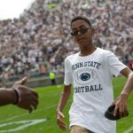 """A young child walking towards a person with their hand out for a handshake on a football field with a white short sleeved t-shirt that says """"Penn State Football""""."""