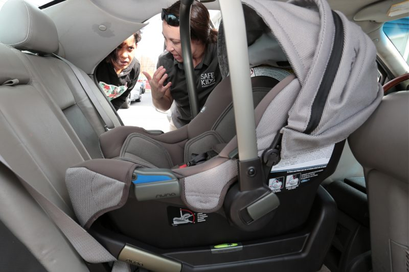 The view from the back seat of a car, across a rear-facing infant car seat, as two women peer in through the opposite side door, talking.