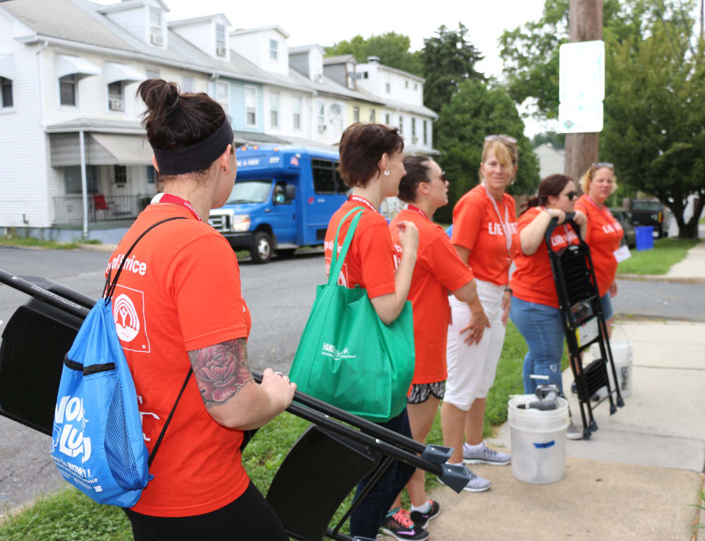 "Six women stand along a sidewalk near a city street. Some hold bags; two are holding step ladders. They all wear orange shirts with the slogan ""LIVE UNITED"" and the United Way logo."
