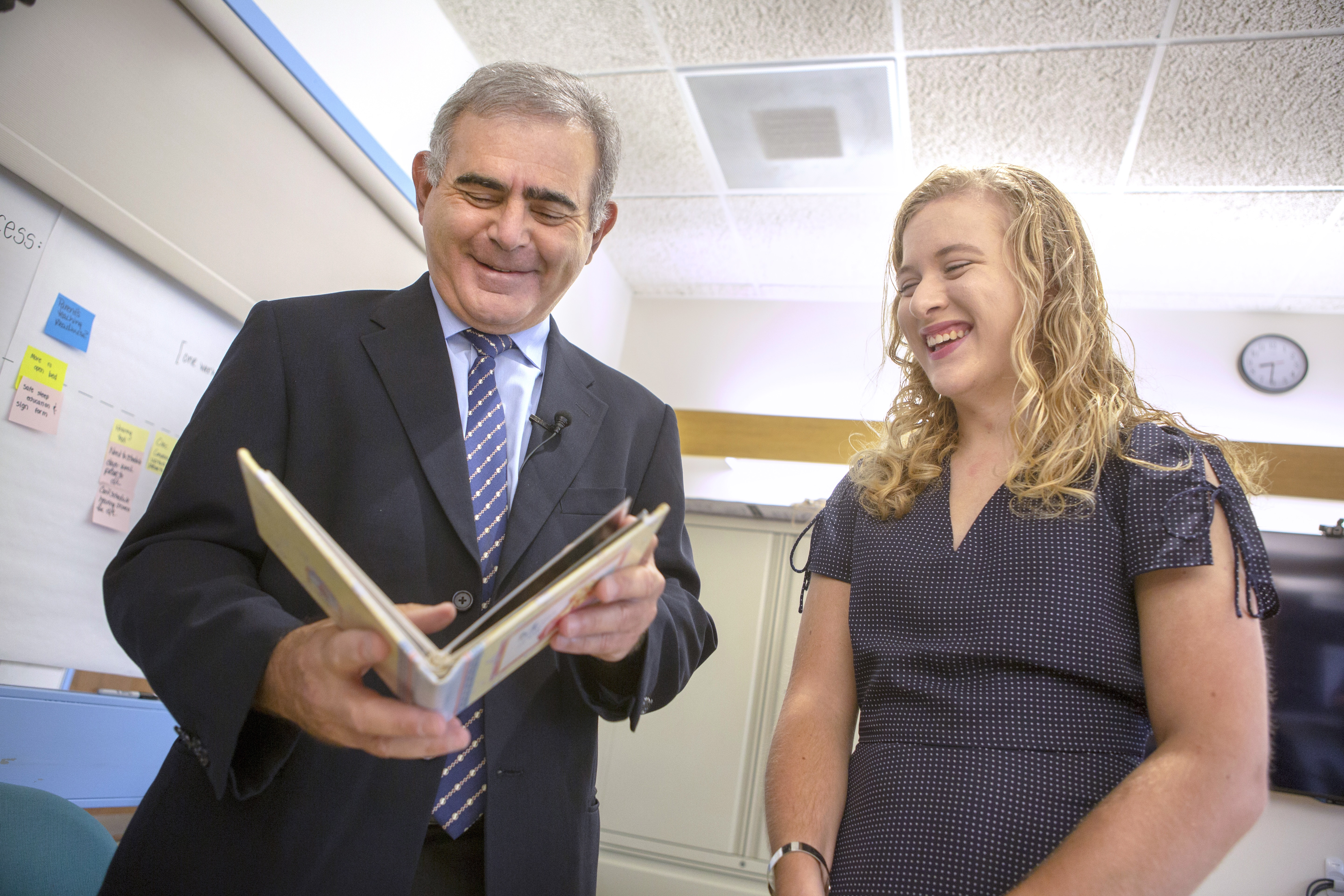 Dr. Charles Palmer, a neonatologist at Penn State Children's Hospital, and Tiffany Seibert, an intern at the Penn State ALS Clinic, smile as they look at a photo album of baby photos of Tiffany when she born prematurely 21 years ago. Dr. Palmer is wearing a suit and tie, and Tiffany is wearing a dress. They are standing in a conference room with a whiteboard, cabinet and clock behind them.
