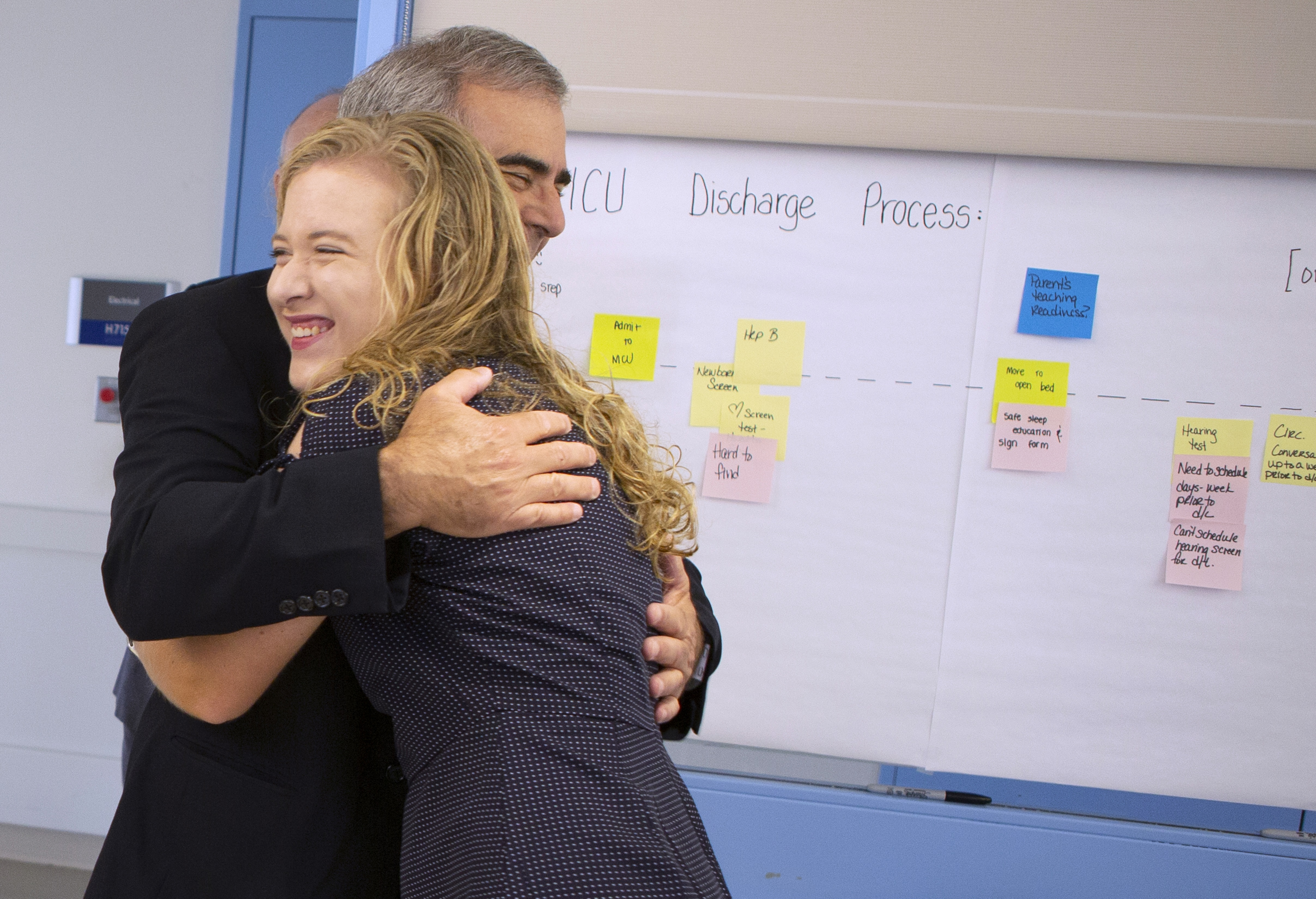 Dr. Palmer and Tiffany Seibert smile and hug during an emotional reunion. Behind them a whiteboard with post-it notes is visible.