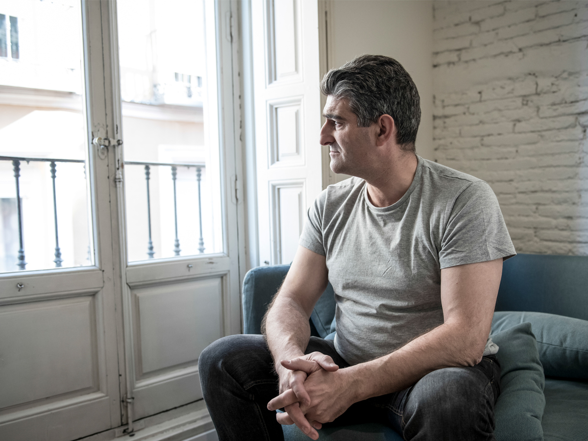 A middle-aged man sits on a couch, looking out the window of the room he's in.