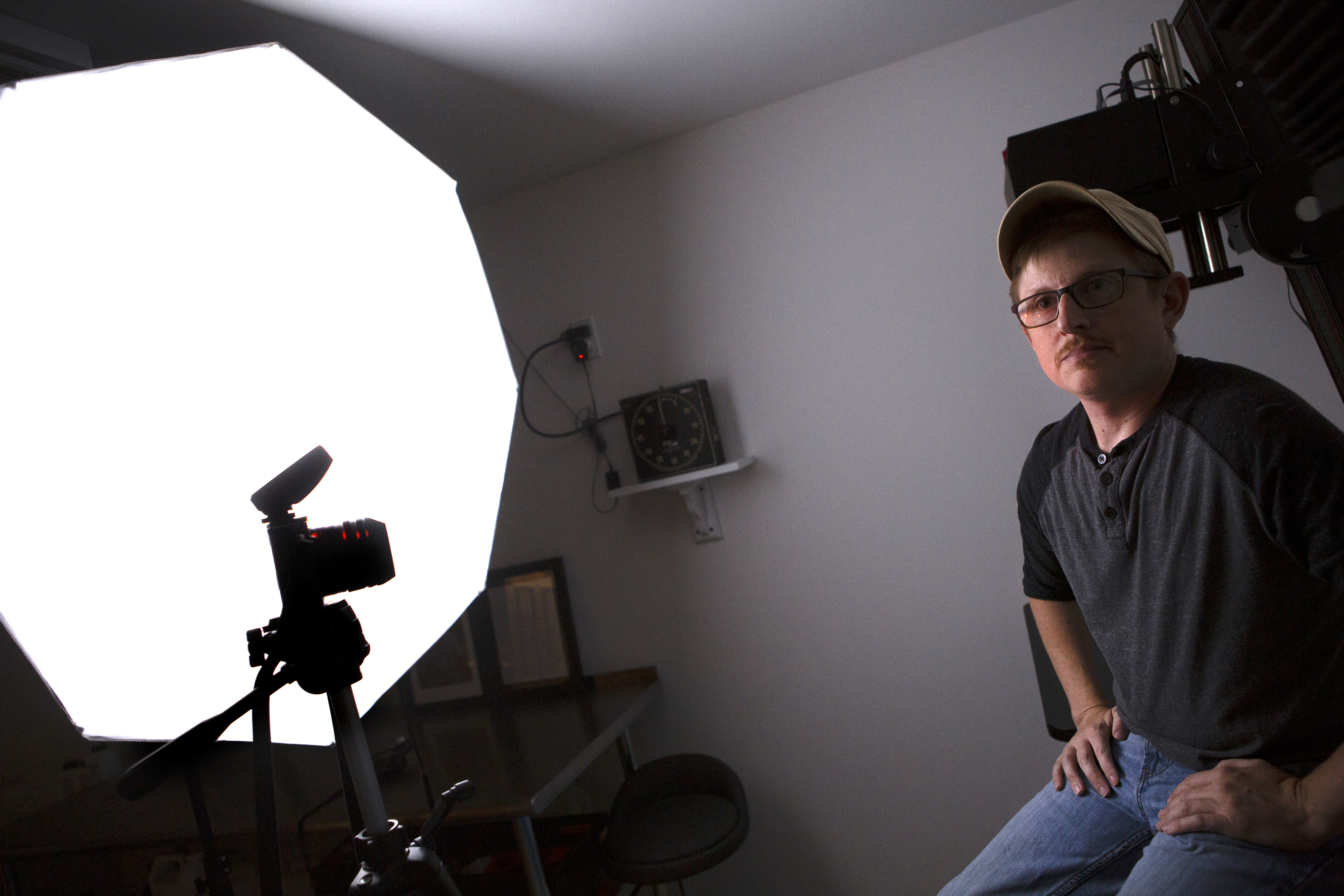 A man wearing a baseball cap, T-shirt and jeans sits in front of a camera on a tripod and an umbrella lamp. In the background is a table, a stool and a timer.