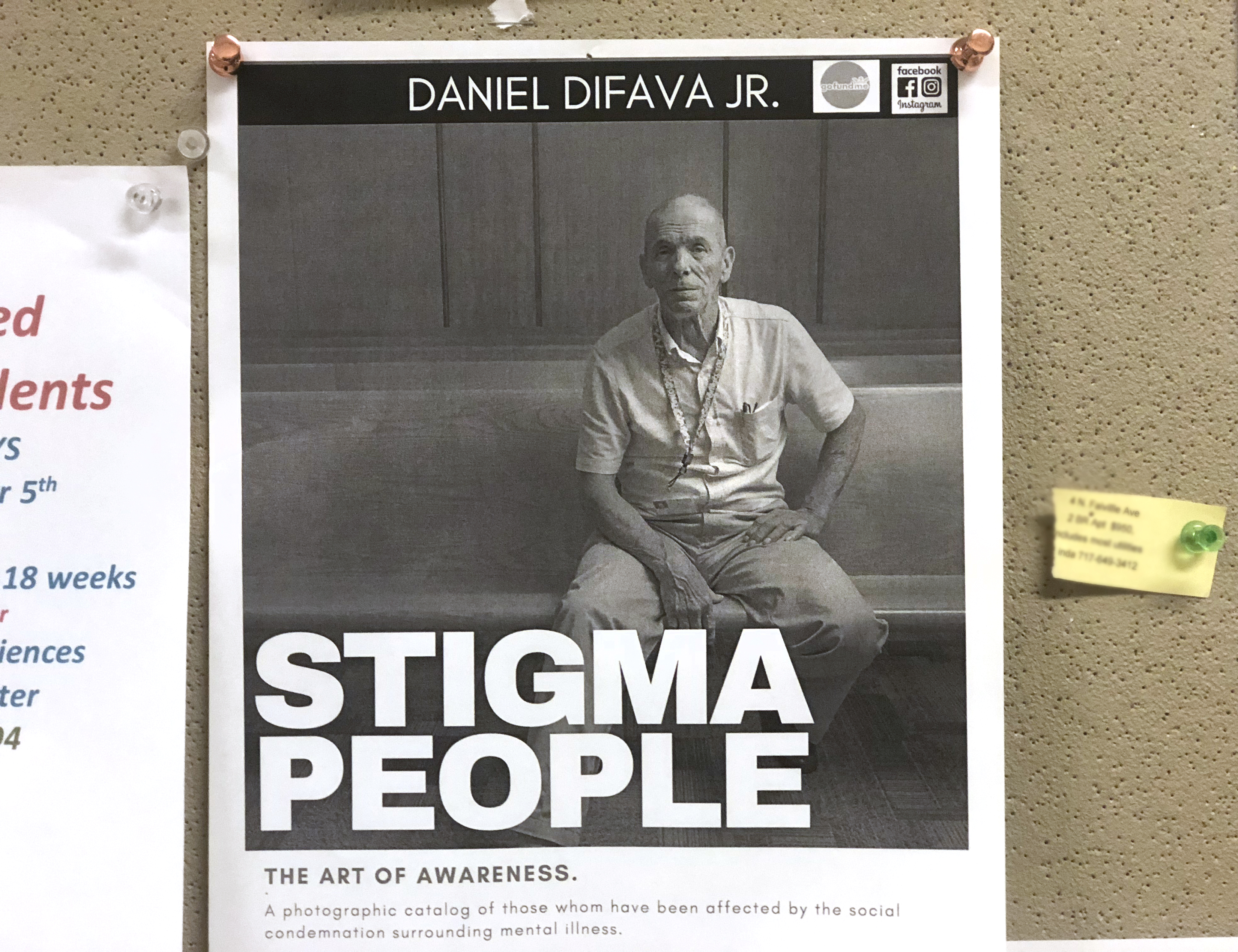 """Poster of """"Stigma People"""" photo exhibit tacked on a bulletin board. Photo is of ol der man sitting on a bench looking seriously at camera. Poster says: """"Daniel DiFava Jr., Stigma People: The Art of Awareness: A photographic catalog of those whom have been affected by the social condemnation surrounding mental illness."""""""