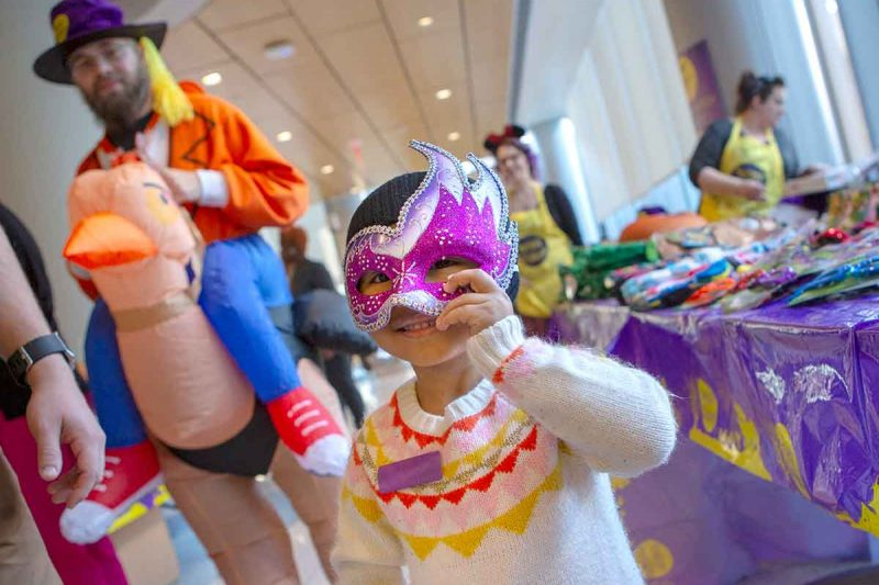 A young girl smiles and holds a mask to her face. She is wearing a sweater and a knit cap. Behind her is a man in a costume as a person riding a turkey and a table of costumes and assorted Halloween items.