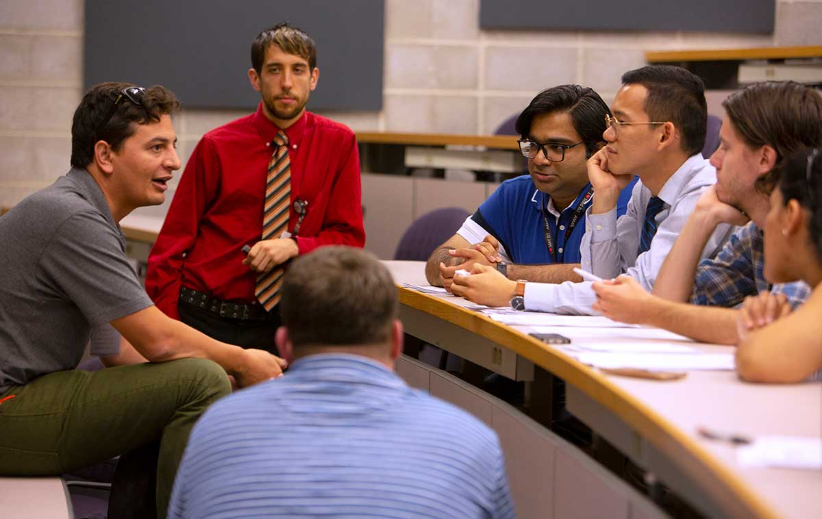 """Six medical students sit at a conference room table and listen to a man talk at the American Medical Association's """"Accelerating Change in Medical Education"""" conference. Behind him Dr. Joshua Davis of Penn College of Medicine, stands and listens."""