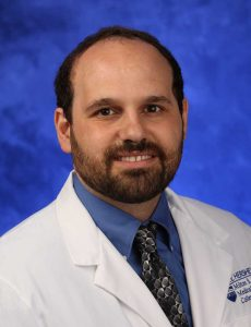 Dr. Michael Freeman of Penn State Health Milton S. Hershey Medical Center/Penn State College of Medicine is pictured in a head-and-shoulders professional portrait wearing a white lab coat with the Penn State Health Milton S. Hershey Medical Center/Penn State College of Medicine logos on it. He has a beard and is wearing a shirt and tie.