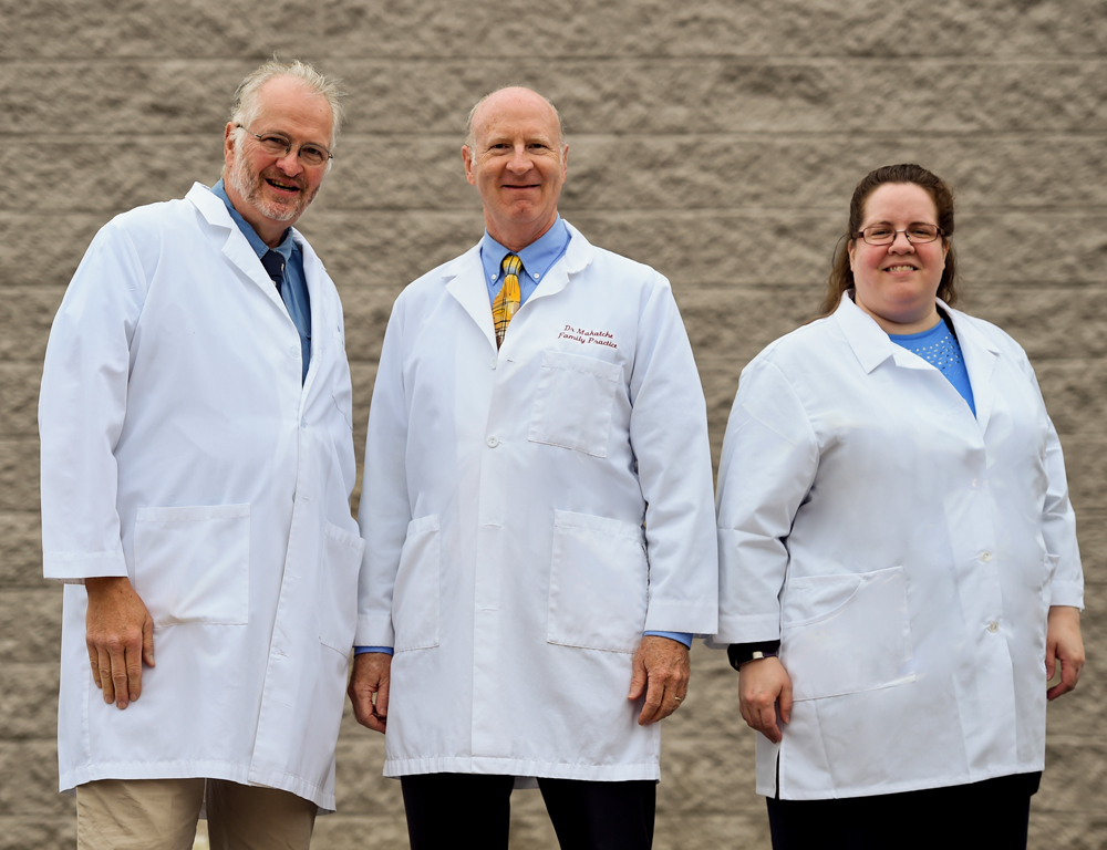 Three people -- two men and one woman -- stand in front of a beige, textured wall, posing for a photo. They're each wearing white clinical jackets.