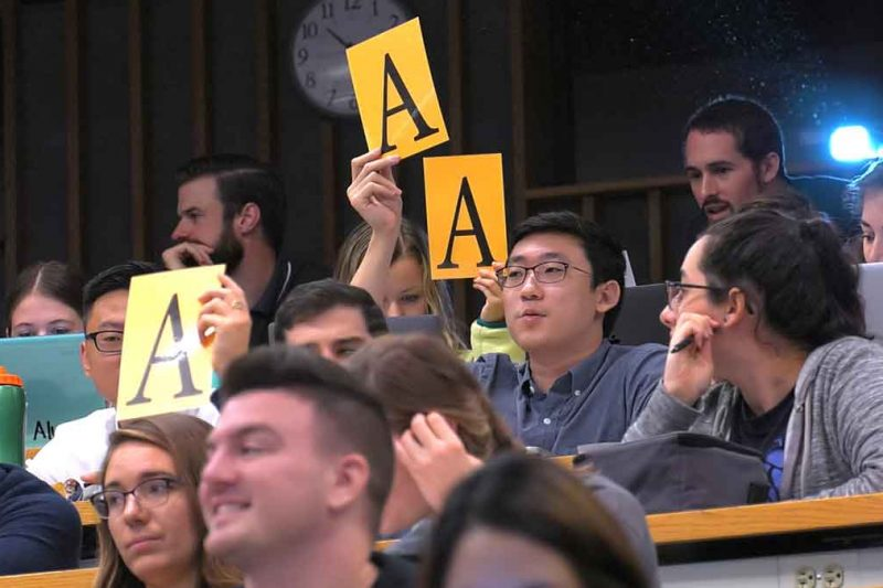 """A group of approximately 12 Penn State College of Medicine students sit in a classroom. Two of them hold up the letter """"A"""" on a large piece of paper. Some are smiling. Behind them is a clock and wooden studs on the wall."""