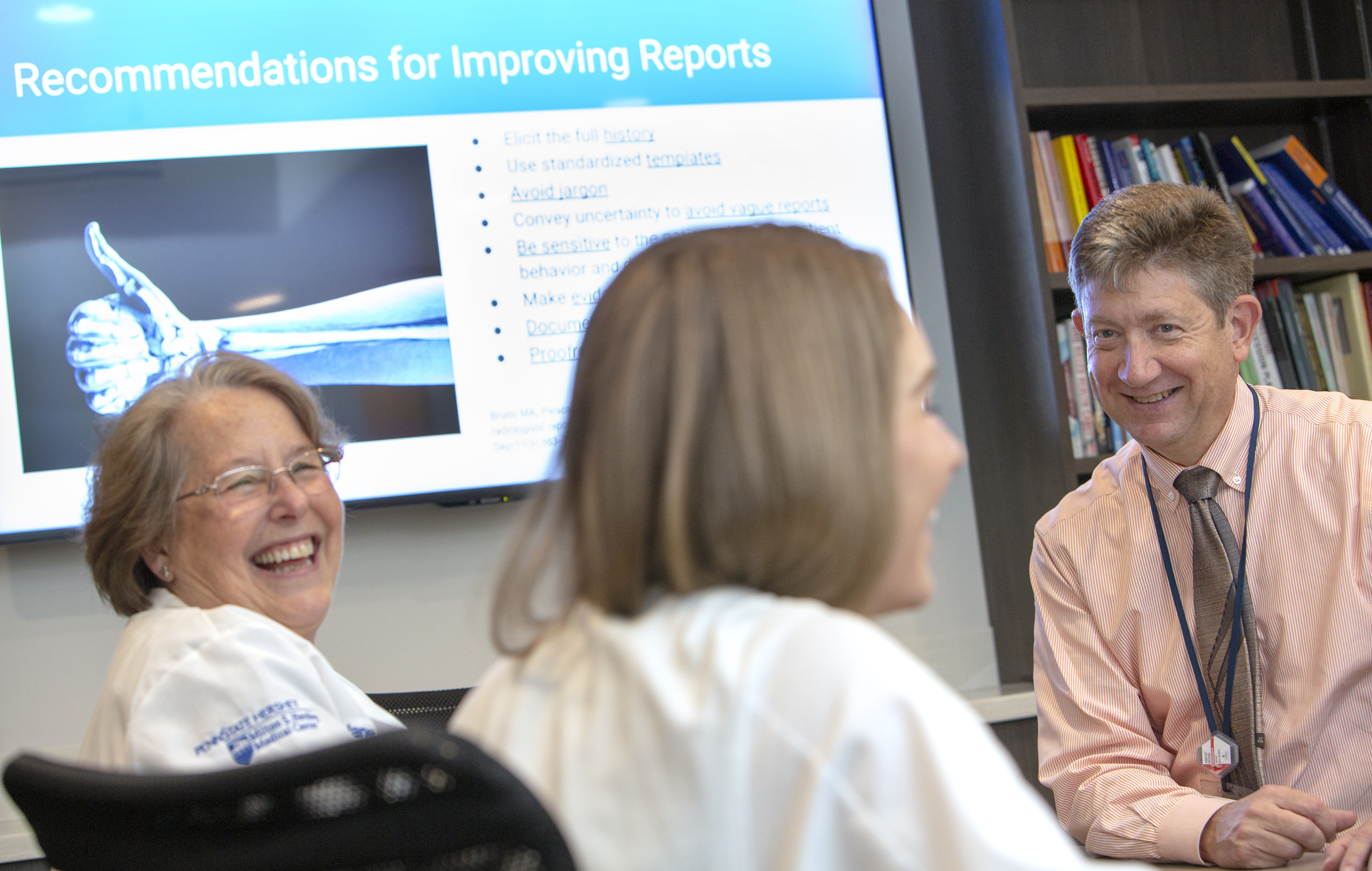 """Dr. Timothy Mosher, chair of the Department of Radiology at Penn State College of Medicine, smiles. Two women wearing white lab coats with the Milton S. Hershey Medical logo on them, smile. Behind them is a PowerPoint slide that says """"Recommendations for Improving Reports"""" and has an image of an arm with a thumb up. Behind Dr. Mosher is a bookshelf with books."""