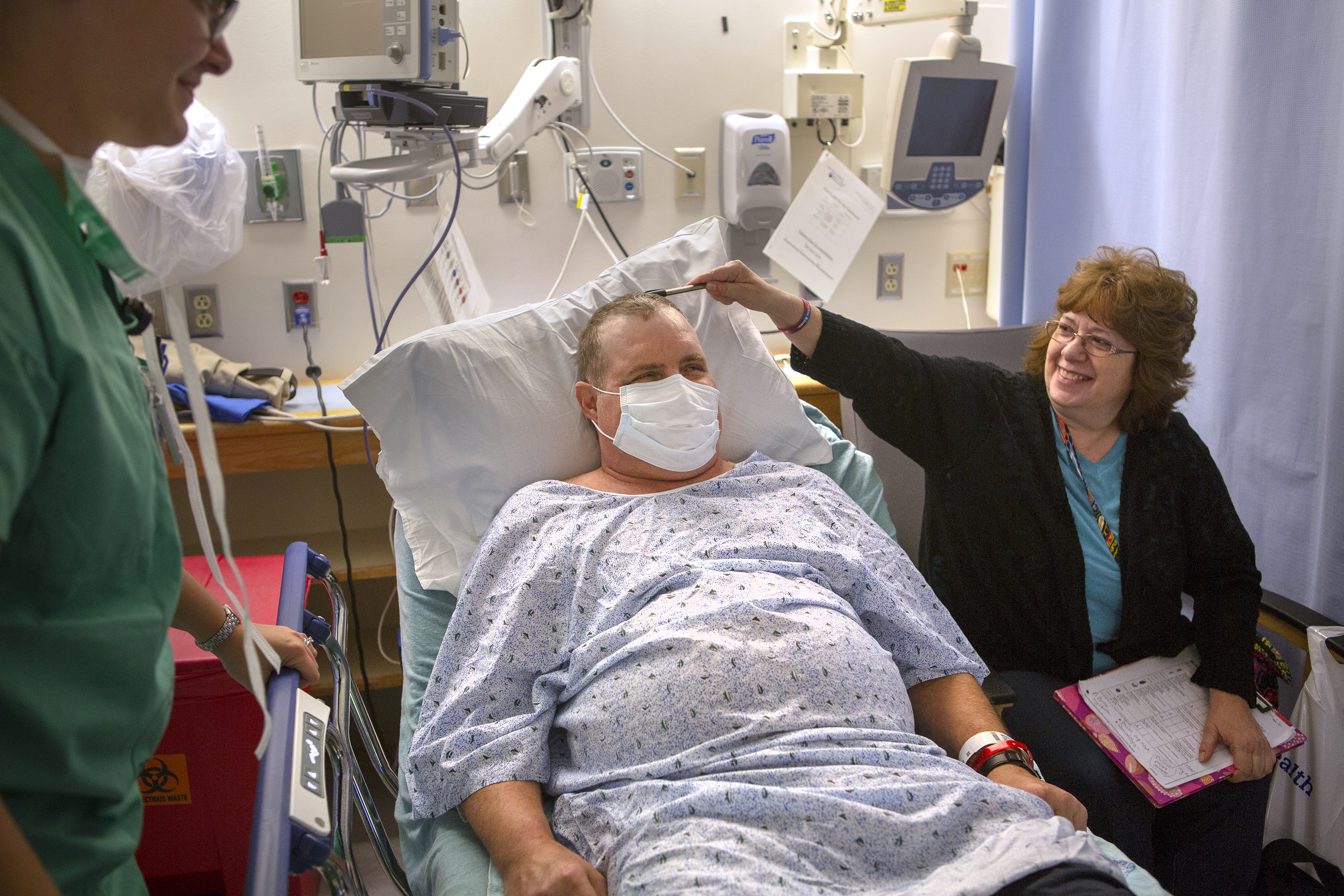 A man wearing hospital gown and mask sits propped up on a hospital bed while his wife sits next to him smiling and touches his head with a pen. A hospital worker stands on the left side and smiles. Behind them is a shelf with medical equipment and cables.