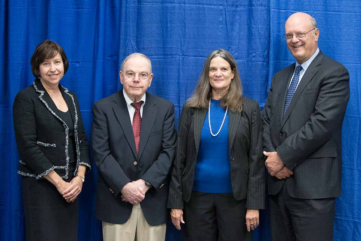 From left, Dr. Leslie Parent smiles with Innovator of the Year Award winners Dr. Joseph Sassani and Patricia McLaughlin and Dr. Craig Hillemeier. They are each wearing business suits and standing in a row smiling. Behind them is a curtain.