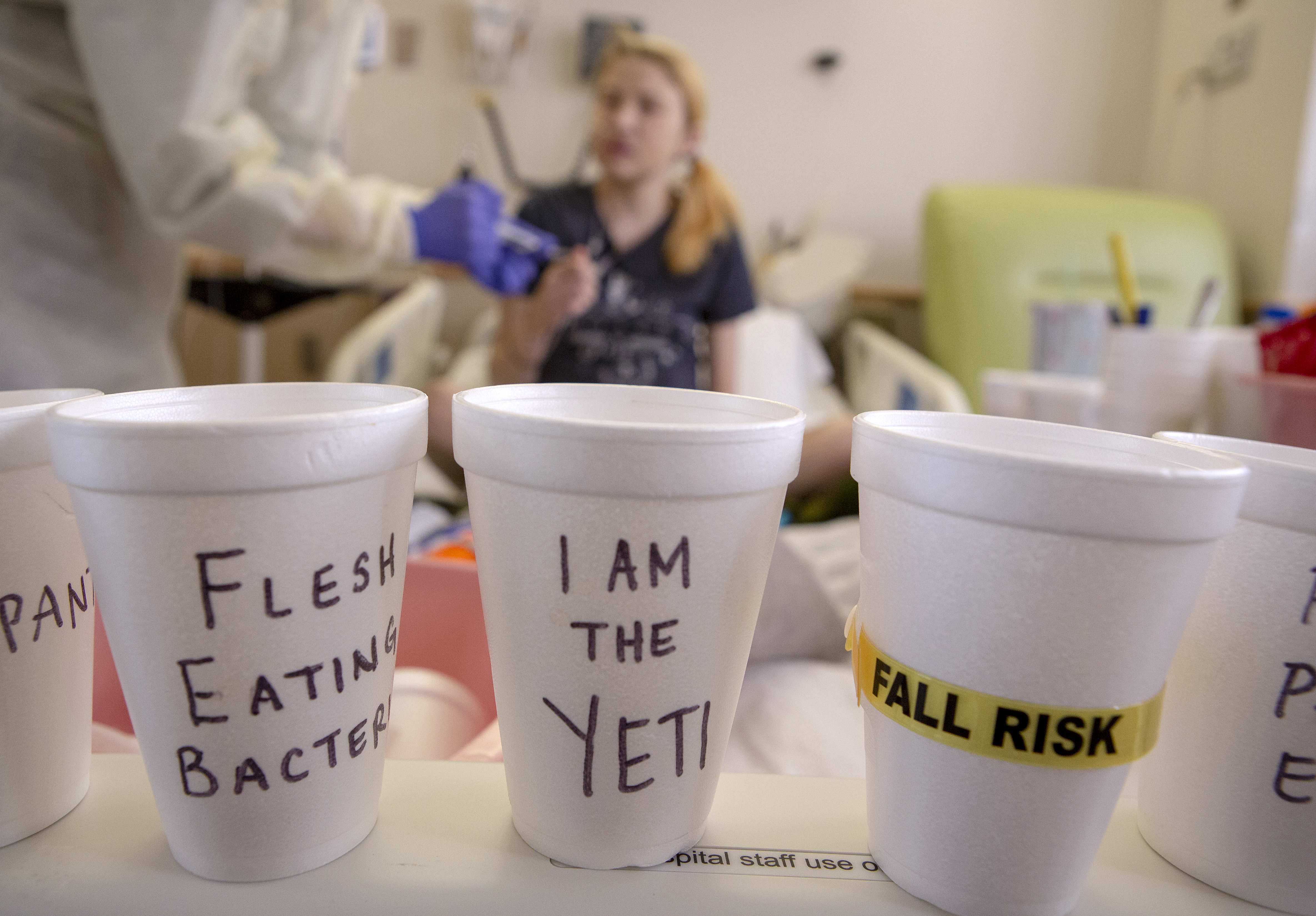 "Three white Styrofoam cups in the foreground say ""Flesh Eating Bacteria,"" ""I am the Yeti"" and ""Fall Risk."" The words are written in Sharpie on the cups. Out of focus in the background, Alyssa Kibler, a 33-year-old cystic fibrosis patient, sits in her bed at Penn State Health Milton S. Hershey Medical Center and talks with a nurse who is seen from the shoulders down. The nurse holds a shot of medication in her hands."
