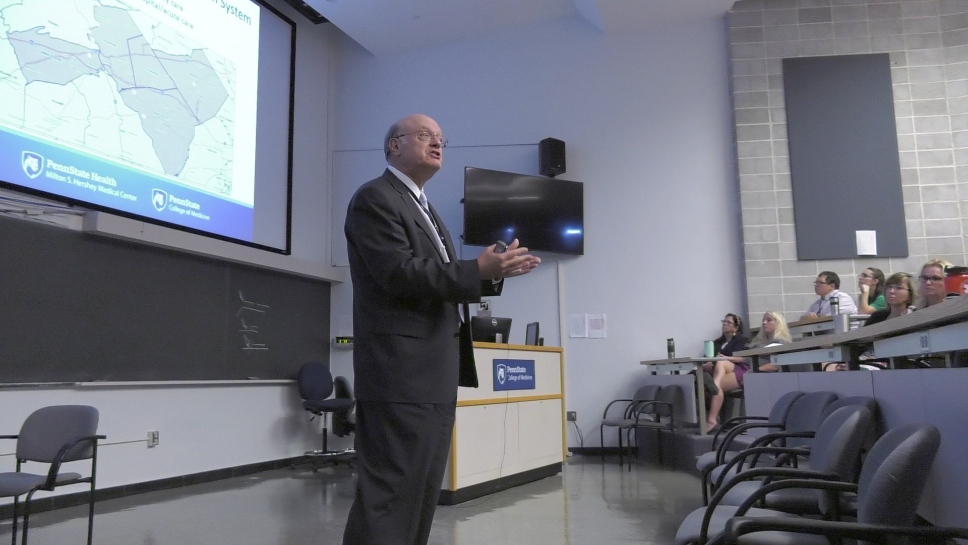 Dr. Craig Hillemeier speaks in front of a class of Penn State College of Medicine students. He is wearing a suit, tie and glasses. Behind him is a screen with a PowerPoint slide of a map. The students are seated in stadium seats. A row of empty chairs is in front of Dr. Hillemeier. On the wall is a large monitor. A gray rectangle is mounted on a brick wall behind the students.