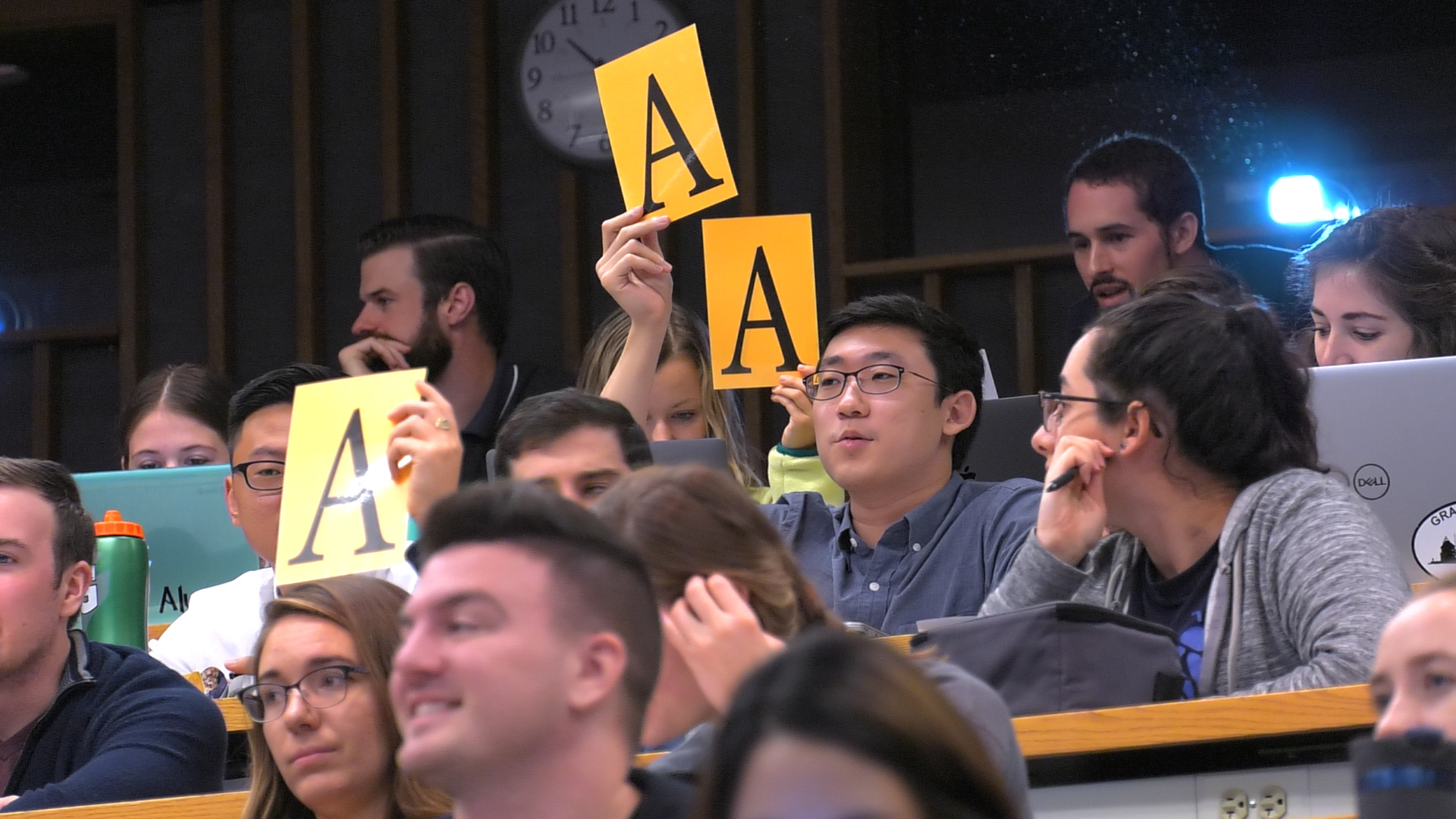 "A group of approximately 12 Penn State College of Medicine students sit in a classroom. Two of them hold up the letter ""A"" on a large piece of paper. Some are smiling. Behind them is a clock and wooden studs on the wall."
