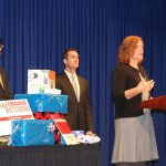 Pediatric Trauma and Injury Prevention manager Amy Bollinger, right, a woman with shoulder-length hair, stands at a podium discussing unsafe toys at a press conference. Behind her stand Reuben Mathew of PennPIRG, left, and Pennsylvania Auditor General Eugene DePasquale, right. Between the two men is a table with wrapped gifts.