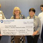 Four woman hold a large posterboard check in the amount of $12,500 made payable to Penn State Health Milton S. Hershey Medical Center. From left are Marie Hankinson, vice president of nursing; Dr. Susan Promes, Emergency Medicine chair; Betty Rigberg of the Association of Faculty and Friends, and Jen Lau, Pediatric Emergency Department nurse manager. Lau is wearing a white lab coat with the Hershey Medical Center logo on it.