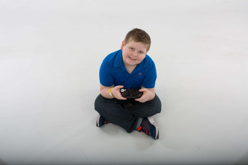 A young boy sits on the floor holding a video game controller with both hands, looking up at the camera, smiling.
