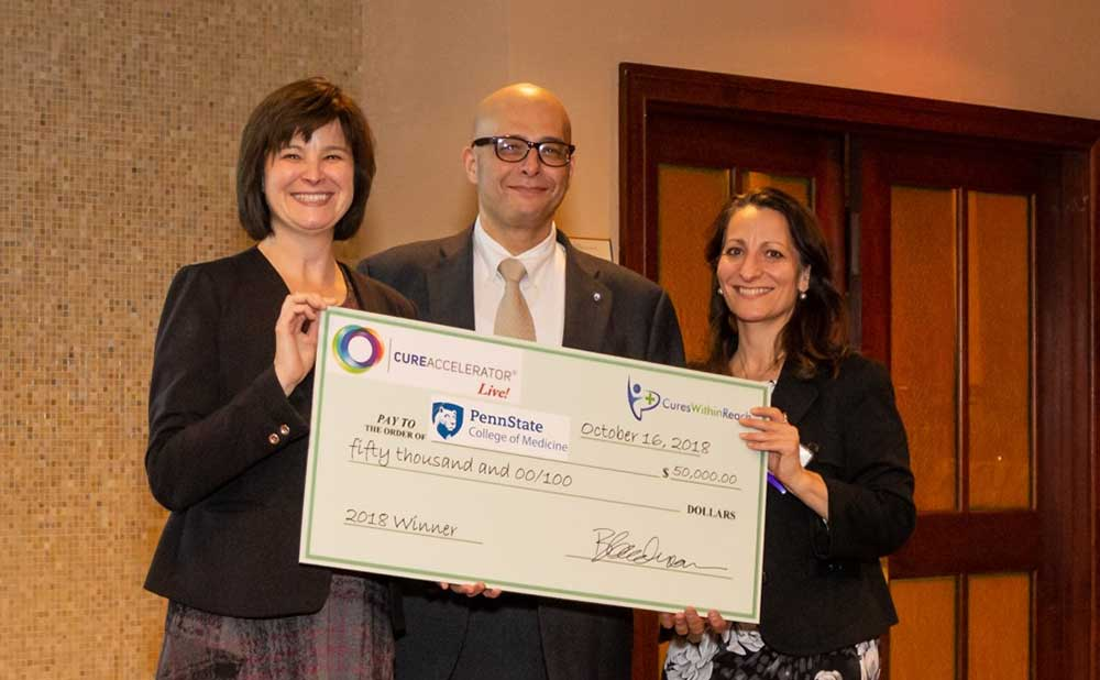 Dr. John Elfar, center, receives a check from Clare Thibodeaux, director of scientific affairs, Cures Within Reach, and Barbara Goodman, president and COO, Cures Within Reach.