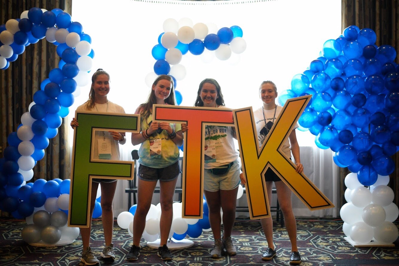 Four teenage girls hold oversized letters that spell out
