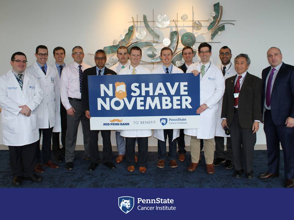 Eleven gentlemen are standing together holding a sign that says No Shave November.