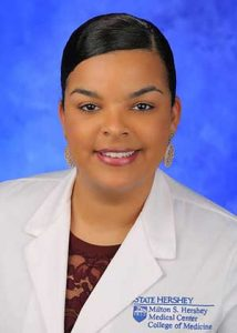 Dr. Sarah Ramirez is seen in a head-and-shoulders professional portrait. She is wearing a white lab coat, a maroon top and gold, dangle earrings.