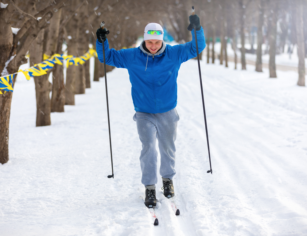 A man wearing winter clothing uses cross-country skis to make his way along a tree-lined road that is coated in a few inches of snow.