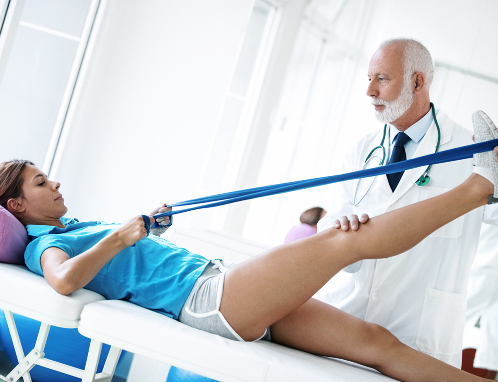 A woman lays on her back on a table, holding a band with both hands. It's looped around her right foot, which is raised in the air. A man in a physician's coat and stethoscope stands next to the table, holding her foot and knee.