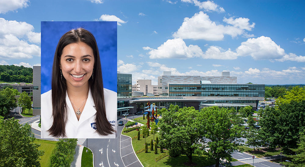 A head-and-shoulders professional photo of student Rhea Sullivan wearing a medical coat is seen superimposed on an image of Penn State Children's Hospital and Penn State Cancer Institute. The buildings are seen from the air, with trees visible in front of them and clouds visible in the sky overhead.
