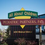 "A sign that says, ""All About Children Pediatric Partners, LLC"" in front of a brick building."