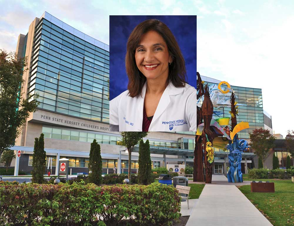 Dr. Debra Byler smiles in a head-and-shoulders professional portrait. She is wearing a white lab coat with the Penn State Children's Hospital logo on the right and her name on the left. She has shoulder-length hair and is wearing a sweater top and a watch.