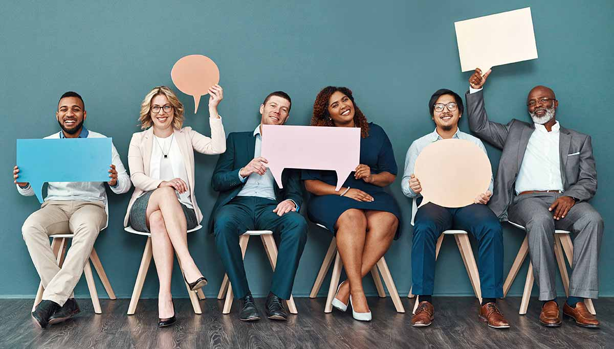 Portrait of a diverse group of businesspeople, four men and two women, holding up speech bubbles while sitting in a row of chairs.